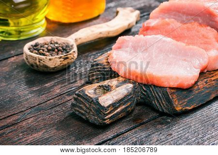 Raw pork meat loin on rustic wooden cutting board. Olive oil, honey and peppercorns on old dark wood table. Close-up angle view