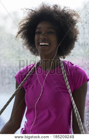 portrait of young afro american woman in gym on workout break while listening music on earphone  and dancing  rainy day and bad weather outdooor poster