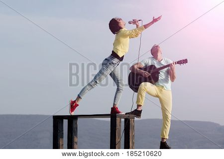 Cute Singer Singing On Table And Handsome Guitarist Playing Guitar