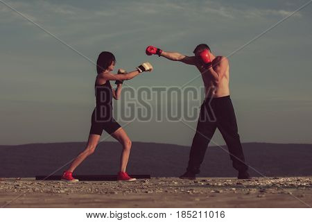 Romantic couple of boxers fighting for love on blue sky. Happy pretty girl or cute woman boxing with handsome man in gloves on sunny summer day on nature. Sport energy and competition