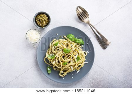 Homemade linguine pasta with green pesto and basil. Italian healthy food concept with copy space, top view.