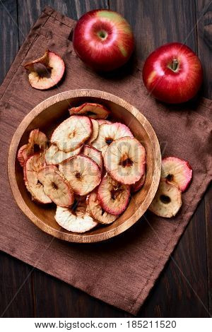 Dehydrated fruits apples chips in wooden bowl healthy snack. Top view