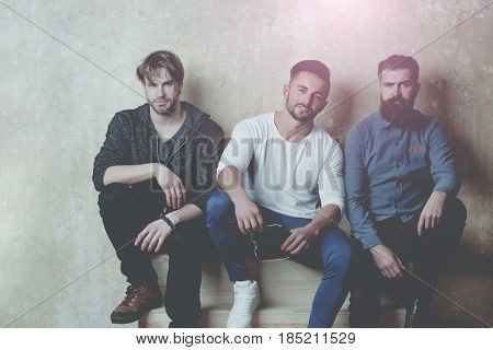 friends. people or men friends with different emotions on faces sitting on wooden stairs on beige wall. Unshaven caucasian models with stylish hair in casual clothes. Beards and haircuts fashion