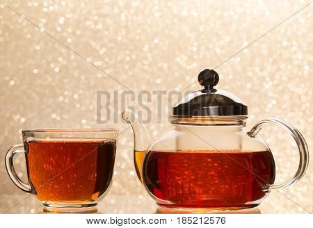 Tea pouring into glass cup and teapot on blur background