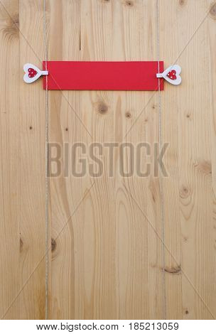Two hearts with clothes pegs and red paper on a cord on wood