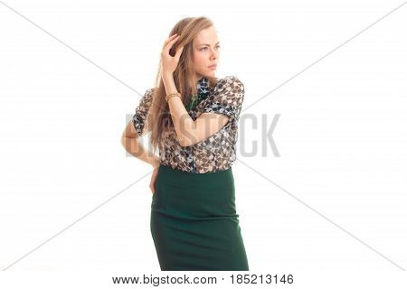 beautiful young girl in green skirt and blouse keeps an arm near hair and looks toward isolated on white background