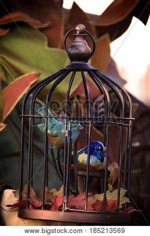 Two porcelain birds in a cage with autumn setting.
