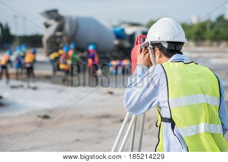 Surveyor worker using theodolite transit equipment at construction site outdoors