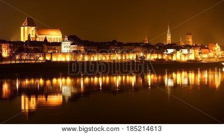 Panoramic View Of Old Town Of Torun At Night Reflected With Many Lights. Reflection In Vistula River
