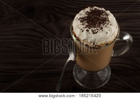 Hot viennese coffee with whipped cream on dark background.