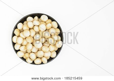 A black bowl of shelled macadamia nuts on a white background
