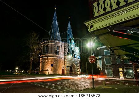 Ancient city gate in the historic city of Kampen at the river IJssel in the province of Overijssel in the Netherlands. Photo photographed during night photography with long shutter speed in the city park. Atmospheric photo shot of a beautiful explanation