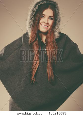 Happy woman wearing dark poncho with furry hood. Winter fashion trendy clothing outfits concept.