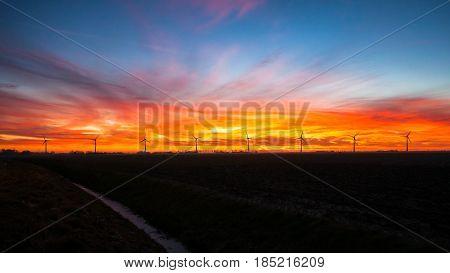 Silhouette of modern windmills for wind energy generation in the dutch polder. Picture taken at sunset in noordoostpolder