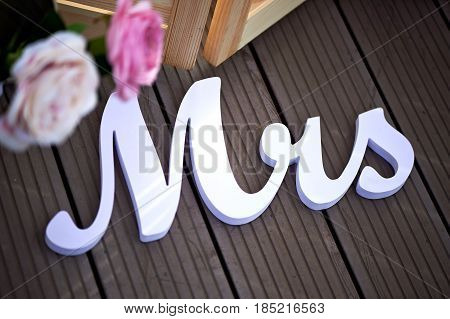 inscription Mrs as decor at the wedding against the dark boards with pink flowers