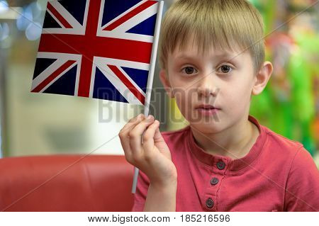 Little boy as a patriot holding in his hand a paper flag of The United Kingdom.