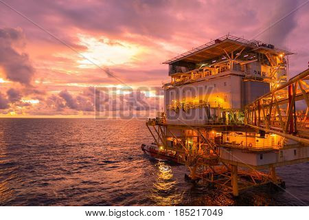 Offshore construction platform living quarter for production oil and gas with bridge in evening time