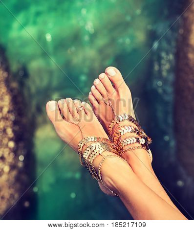 Perfect clean female feet  with sea sand on the beach . Spa ,scrub and foot care . Foot massage . Jewelry for the feet .