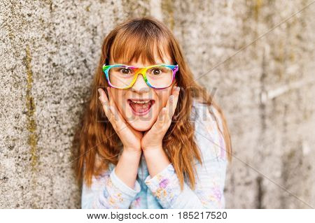 Little redhead girl wearing rainbow eyeglasses. Hands on cheeks looking at the camera with astonished or shocked expression, mouth wide open.