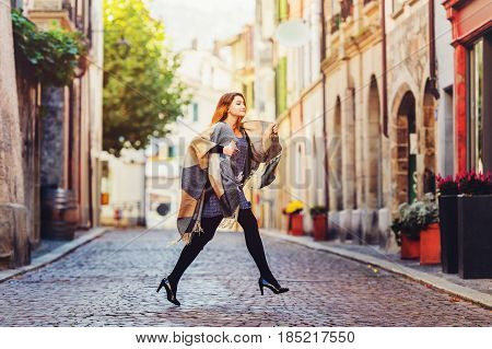 Young fashion 20 year old girl with red hair running down the street, wearing light dress, black tights, high heel shoes and warm plaid jacket