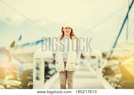 Outdoor fashion portrait of young preteen kid girl wearing white cap, faux fur gilet, playing in a port on a very sunny day, toned image