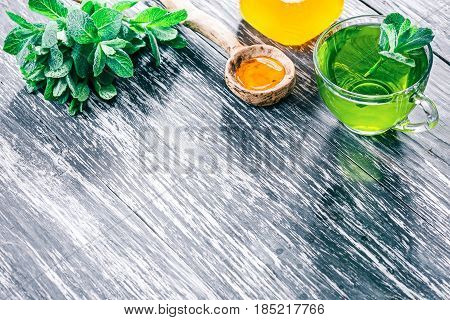 Green mint tea in translucent glass tea cup with honey and fresh mint leaves on textured black wood background