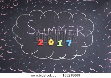 Summer chalk and multi-colored figures 2017 on a dark background of a slate in a frame drawn