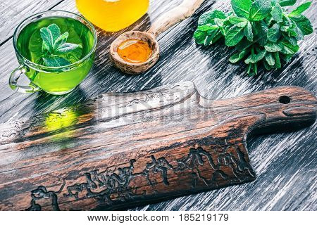 Green mint tea in translucent glass tea cup with honey and fresh mint leaves on textured black wood background with rustic wooden serving board