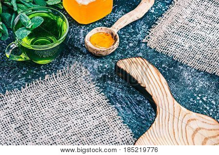 Green mint tea in translucent glass tea cup and honey in rustic wooden spoon on textured spotty background. with fresh mint and wooden serving board and burlap