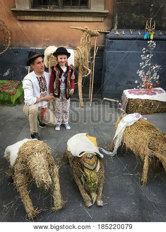 LVIV UKRAINE - MAY 06: Photo for tourists dressed in Ukrainian national dress on the background of haystack on May 06 2017 in Lvov Ukraine
