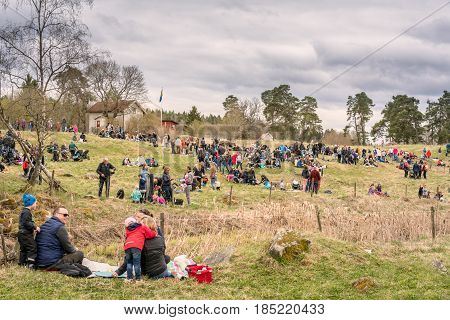 People having picnic on grass hill. Vallentuna, Sweden - May 06, 2017: Many people sitting and laying on grass hill and field having picnic. Landscape view of families children and adults outdoors.