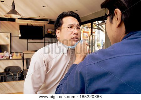 Two young businessmen are fighting in a coffee shop.