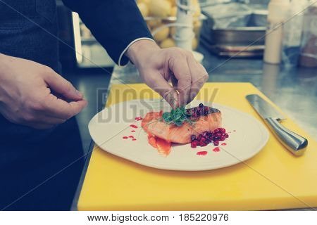 Chef is decorating fried salmon steak with green pea, work at commercial kitchen, toned image