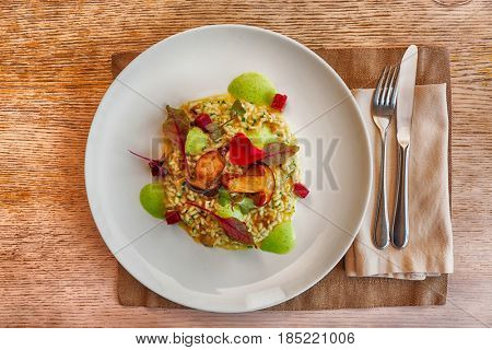 Risotto with fried porcini mushrooms on plate, place setting in a restaurant, toned image