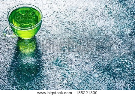 Green mint tea in translucent glass tea cup on textured spotty background