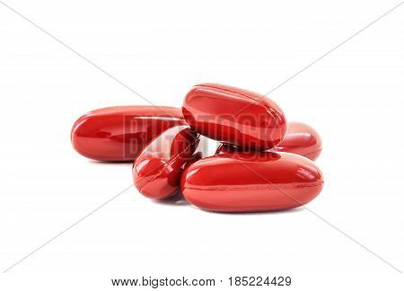 Red supplement capsules for healthcare isolated on white background