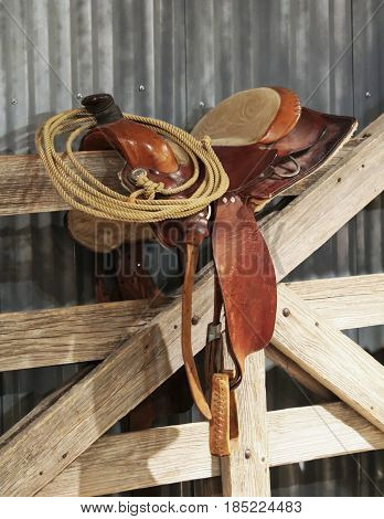 A Saddle and a Lariat on a Wooden Gate Against a Tin Wall