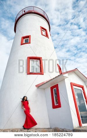 Sexy girl in red dress stands near the lighthouse on a Sunny summer day. Beautiful summer weather vacation at sea. The woman on the background of lighthouse and blue sky with white clouds
