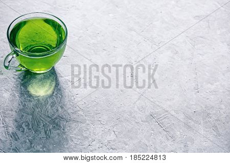 Green mint tea in translucent glass tea cup on concrete background