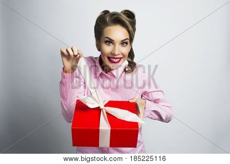 Happy beautiful funny woman unpacks gift in red box