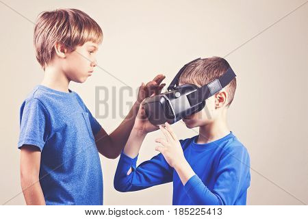 Kids trying virtual reality VR glasses at home.