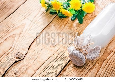 Buttermilk in glass bottle. Raw wood background with dandelions. Selective focus