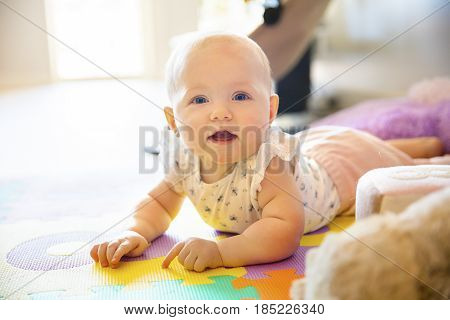 Smiling baby girl with blue eyes playing on the floor with toys on a playmat. A cute young child plays and smiles.