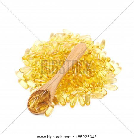 Pile of yellow softgel medical pills with a wooden spoon over it, composition isolated over the white background