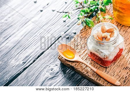 Ricotta with jelly, honey and almonds in glass jar. Textured black wood background with apple blooming twigs. Selective focus
