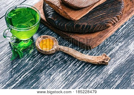 Green tea in translucent glass tea cup with fresh mint, honey and wooden tableware on textured black wood background