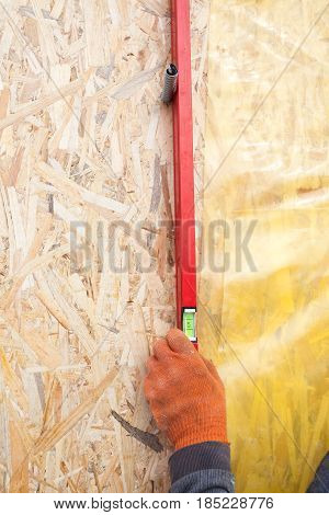 Builder ensuring that a wall is vertical holding a builders level