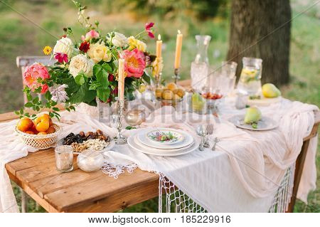 picnic, food, summer, holiday concept - festively decorated wooden picnic table among trees, bouquet, pitcher of lemonade, glasses, fruit plates, candlesticks, vegan food, selective focus