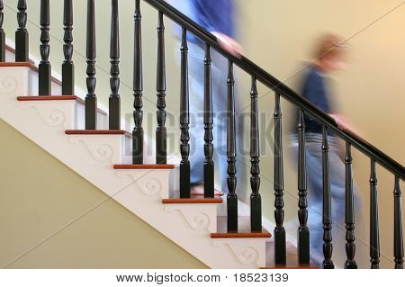 Man and woman rushing down stairs