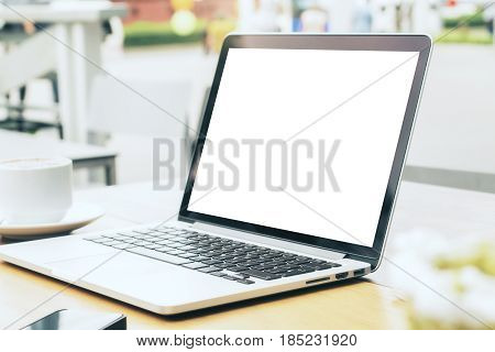 Side view and close up of blank white laptop placed on wooden cafe table with coffee cup smartphone and other items. Mock up